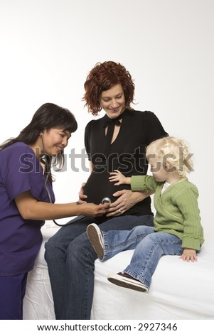 Nurse holding stethoscope on Caucasian pregnant woman's belly. - stock photo