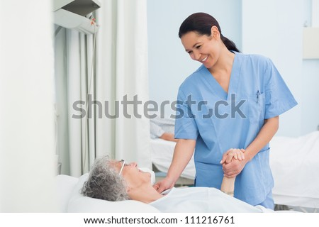 Nurse holding the hand of a patient in hospital ward - stock photo