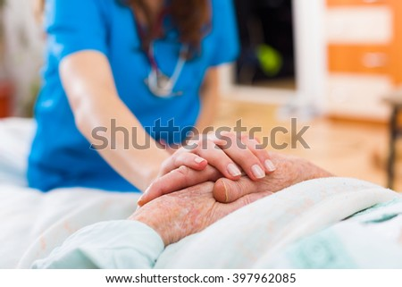 Nurse holding the hand of an elderly woman, showing sympathy and kindness. - stock photo