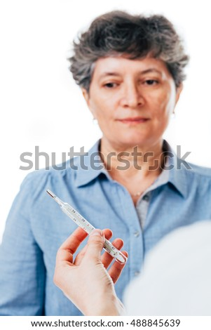 Nurse holding thermometer in front of senior patient feeling sick