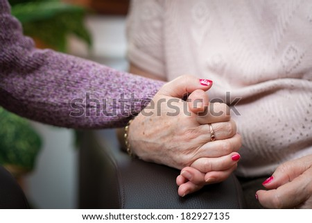 Nurse holds the senior woman hands - stock photo