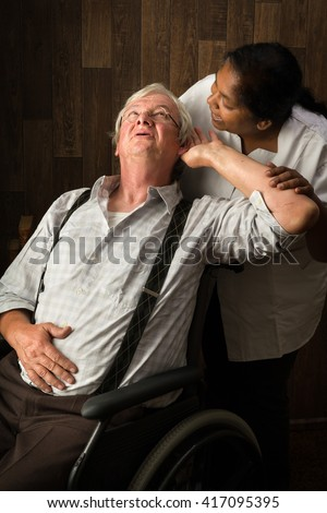 Nurse in a home talking loudly to a hearing impaired elderly man - stock photo
