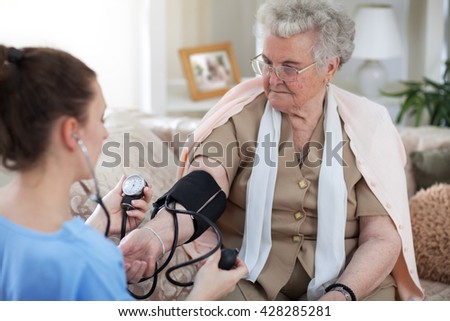 Nurse in home visit measuring blood pressure of old woman - stock photo