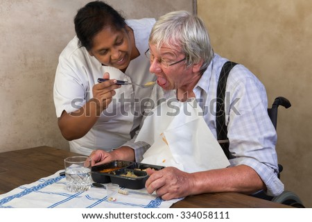 Nurse in old people's home trying to make a patient eat his dinner - stock photo