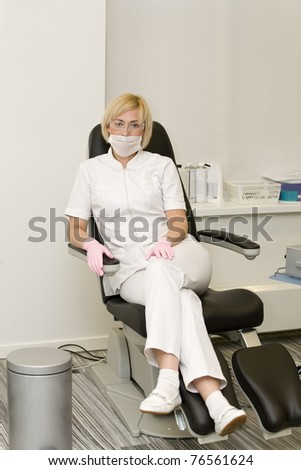 Nurse in respiratory bandage is sitting on pedicure chair