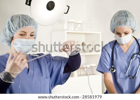 Nurse injecting with syringe into a iv tube - stock photo