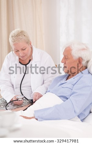 Nurse is checking the pulse of her patient