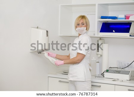 Nurse is pulling a napkin to wipe her hands - stock photo
