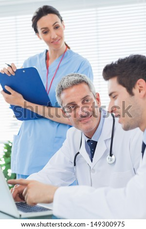 Nurse listening to doctors talking about something on their laptop in medical office - stock photo