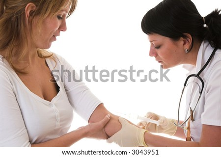 Nurse looking where the right vein is to inject her needle in while her patient looks a bit scared