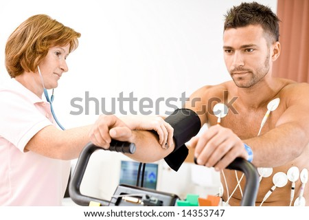 Nurse makes the patient ready for medical EKG test. Real people, real locacion, not a staged photo with models. - stock photo
