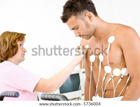 Nurse makes the patient ready for medical EKG test. Real people, real location, not a staged photo with models. - stock photo