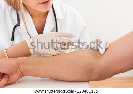 Nurse making injection to patient in clinic - stock photo