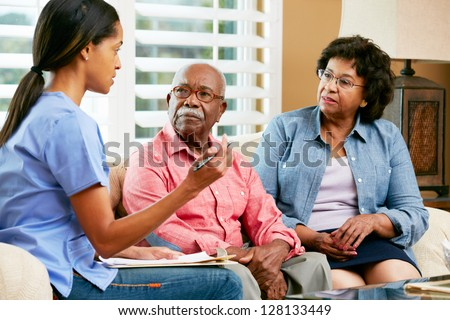 Nurse Making Notes During Home Visit With Senior Couple - stock photo