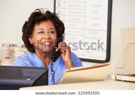 Nurse Making Phone Call At Nurses Station - stock photo