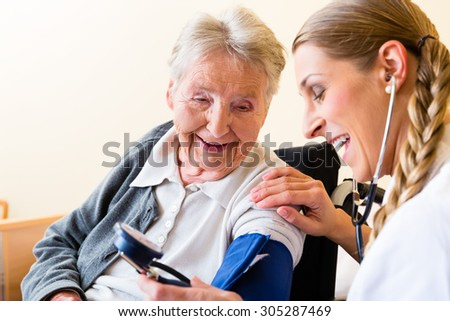 Nurse measuring blood pressure at senior woman patient in retirement home - stock photo