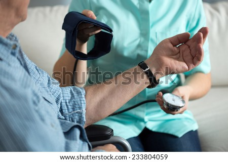 Nurse measuring blood pressure of handicapped man - stock photo