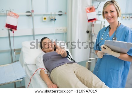 Nurse next to a patient while holding a clipboard in hospital ward - stock photo