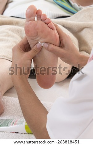 Nurse or care giver  treating  a senior woman's foot - stock photo