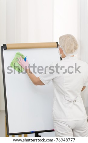 Nurse or doctor is wiping a board - stock photo