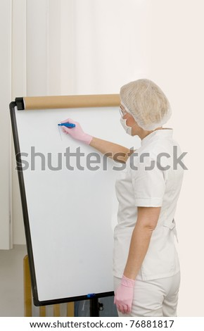 Nurse or doctor is writing on the board - stock photo