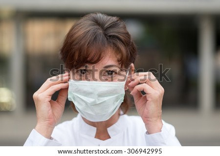 Nurse or doctor wearing a face mask outdoors as protection against an airborne virus or bacteria holding her hands to her cheeks