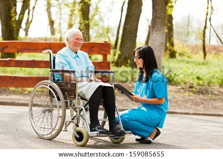 Nurse or doctor writing on chart near elderly patient in wheelchair. - stock photo