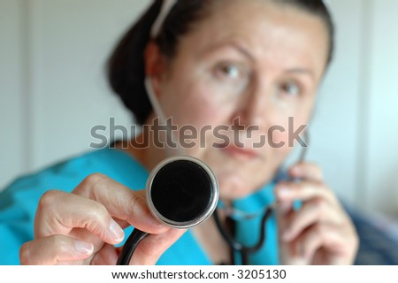 Nurse performing a checkup with a stethoscope; selective focus on the hand holding the apparatus - stock photo