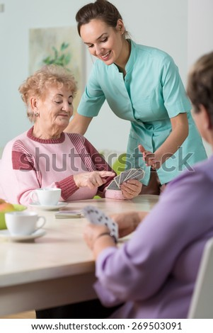 Nurse playing cards with elderly women - stock photo