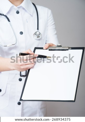 Nurse pointing to clipboard  - stock photo
