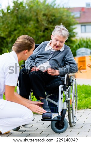 Nurse pushing senior woman in wheelchair on walk thru garden in summer - stock photo