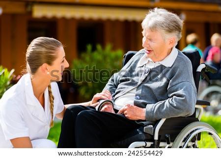 Nurse pushing senior woman in wheelchair on walk thru garden in summer - stock photo