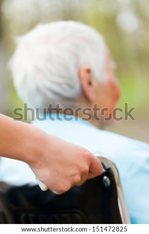 Nurse pushing wheelchair outdoors with senior patient. - stock photo