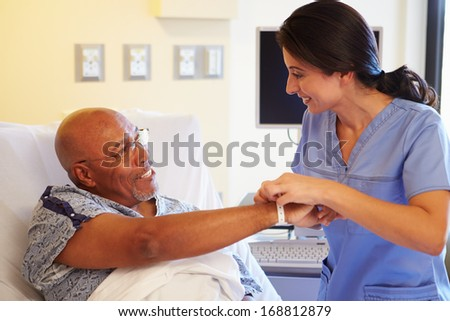 Nurse Putting Wristband On Senior Male Patient In Hospital - stock photo