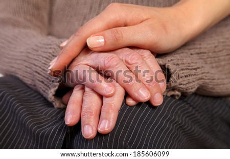 Nurse's hand comforting an elderly woman's wrinkled hand.