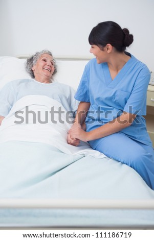 Nurse sitting on the medical bed next to a patient in hospital ward - stock photo