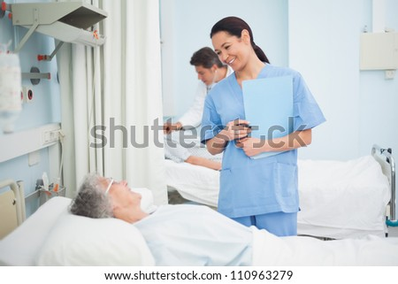 Nurse smiling to a patient in hospital ward - stock photo