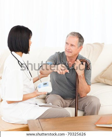 Nurse taking blood pressure of her patient - stock photo