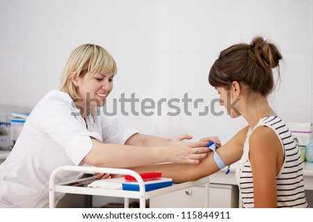 Nurse taking blood sample  from patient in clinic