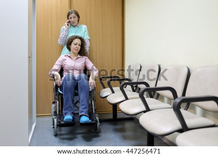 Nurse talking on phone in hospital corridor, standing next to patient in wheelchair, holding handles - stock photo