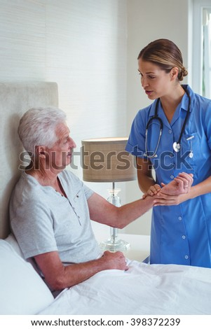 Nurse talking to senior man while examining at home - stock photo