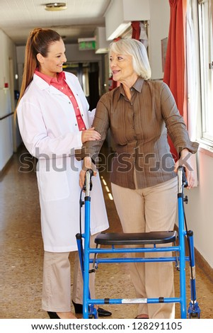 Nurse talking to senior patient with walker in hospital - stock photo