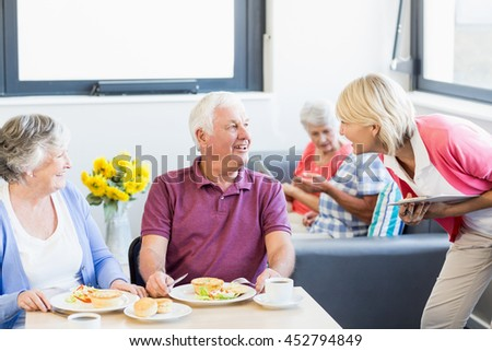 Nurse talking to seniors in a retirement home - stock photo
