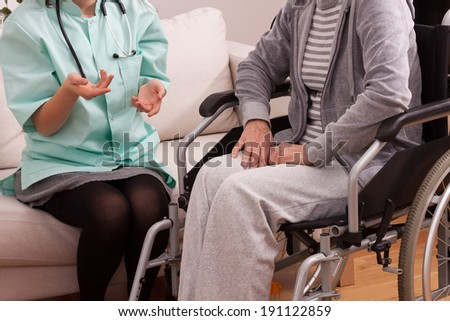 Nurse talking with disabled patient at home - stock photo