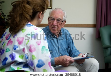 nurse talking with senior man - stock photo