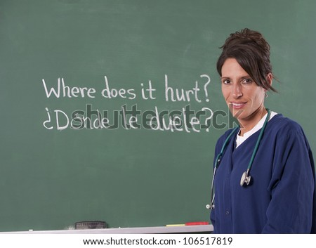 Nurse teacher translating English to Spanish on chalkboard of classroom. Focus is on teacher. - stock photo