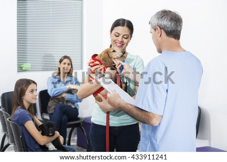 Nurse Touching Dachshund Carried By Woman In Waiting Area - stock photo