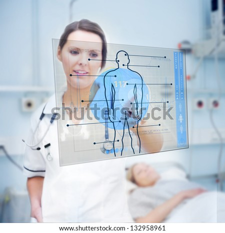 Nurse touching screen displaying blue human form in hospital ward - stock photo