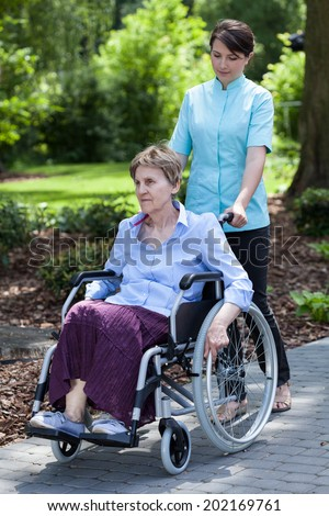Nurse walking with disabled lady in a garden