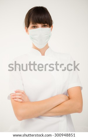 Nurse wearing protective mask with arms crossed on white background - stock photo